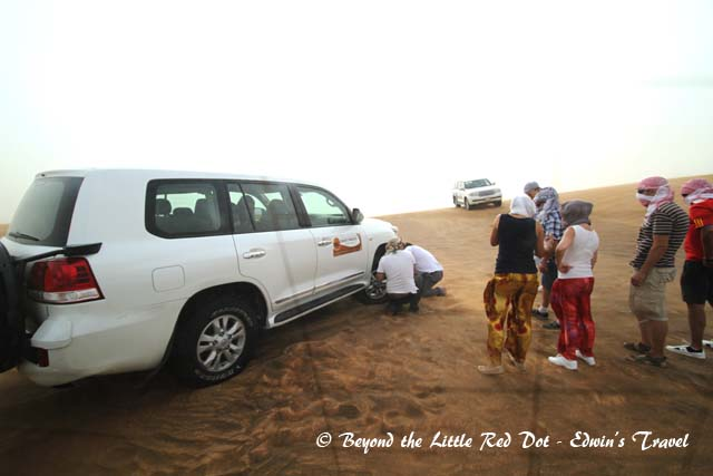 The tyres have to be deflated to get better grip on the sand. This land cruiser had its front tyre dislodged from the rim due to the low pressure. They are trying to fix it back.