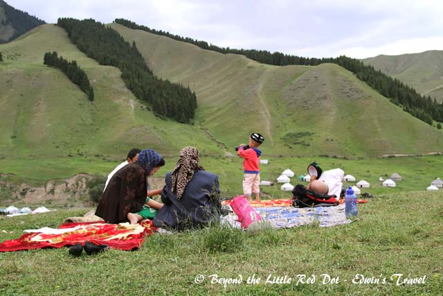 A Kazakh family enjoying a picnic on top of a hill.