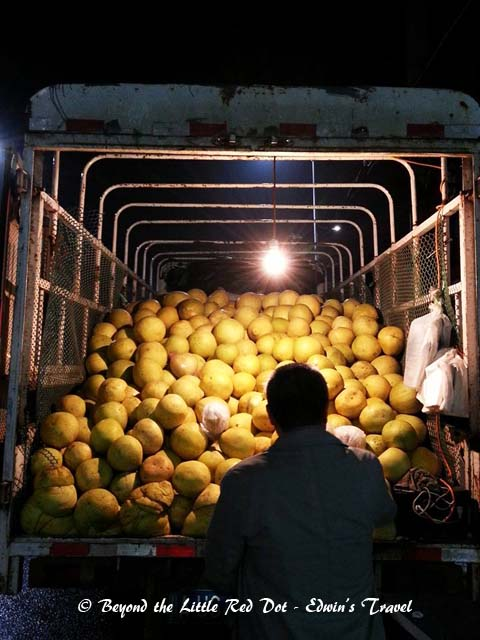 With the bad weather, we decided to go back to our hotel. Here we are, buying melons from the back of a truck on the road side.