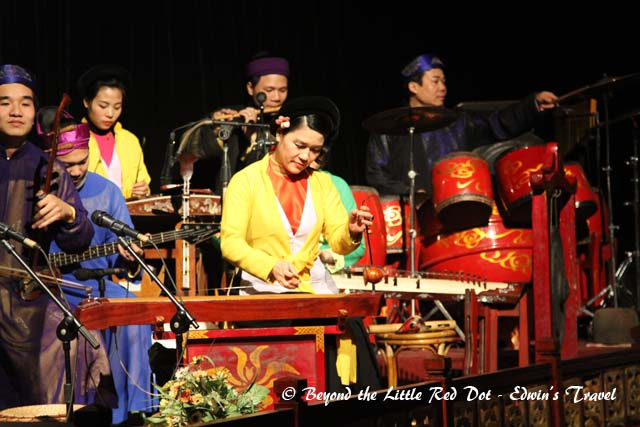 The performance is accompanied by a live orchestra of traditional Vietnamese instruments.