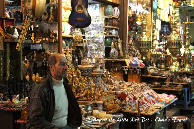 A shopkeeper sitting in front of his shop.