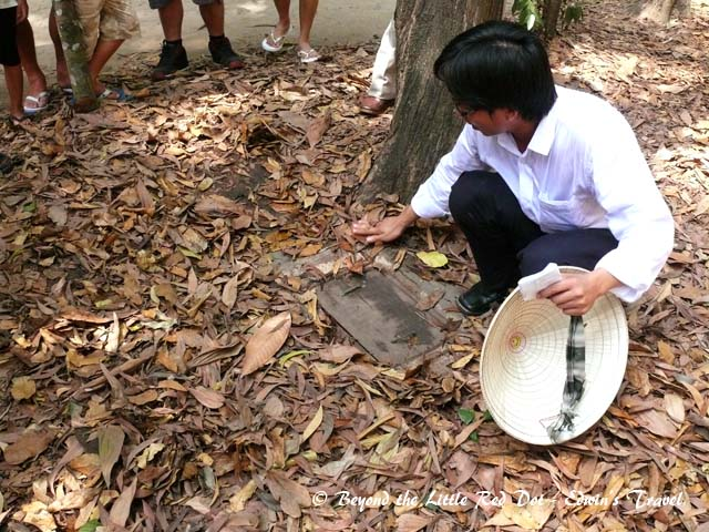 The guide show us a trapdoor which leads to the Cu Chi tunnels.