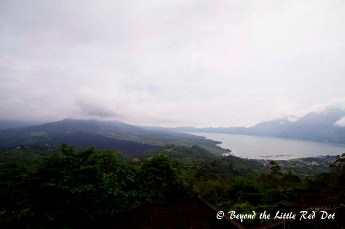 Mt Batur on the left hidden in clouds, Lake Batur on the right with the cauldera rim. The black lava from the last eruption can be seen.