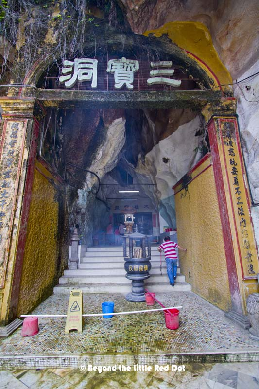 An incense burner in front of the cave's mouth.