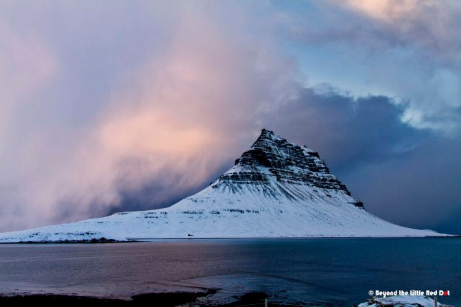 Kirkjufell with storm clouds coming up around it.