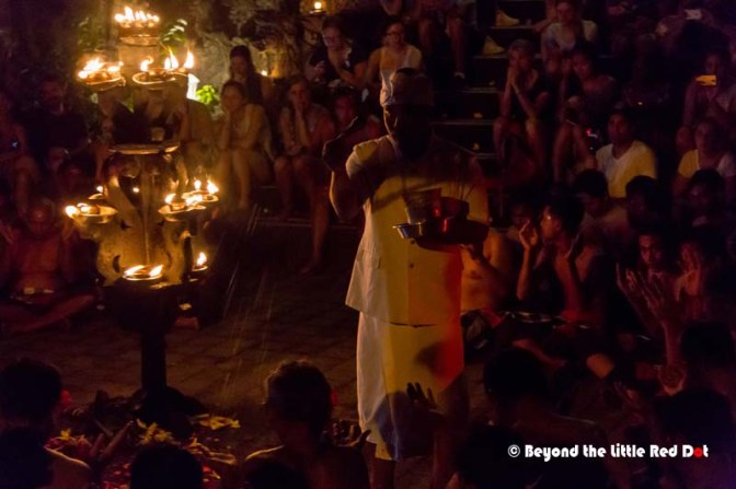 The priest goes around blessing the performers with holy water.