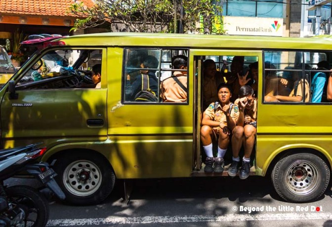The 'forever' traffic jam that happens everyday in Ubud town center. School children pack into a school bus on their way home.