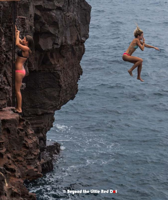 Divers jump into the ocean and climb back up using the metal ladder on the cliff.